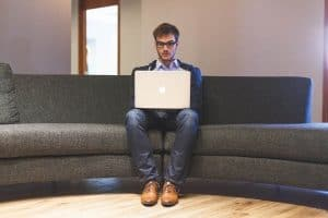 Main with laptop sitting on his own on a large sofa