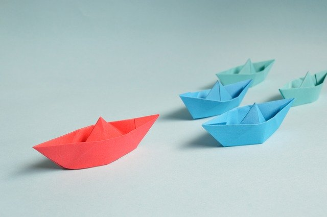 blue paper boat in front of red paper boats signifying leadership